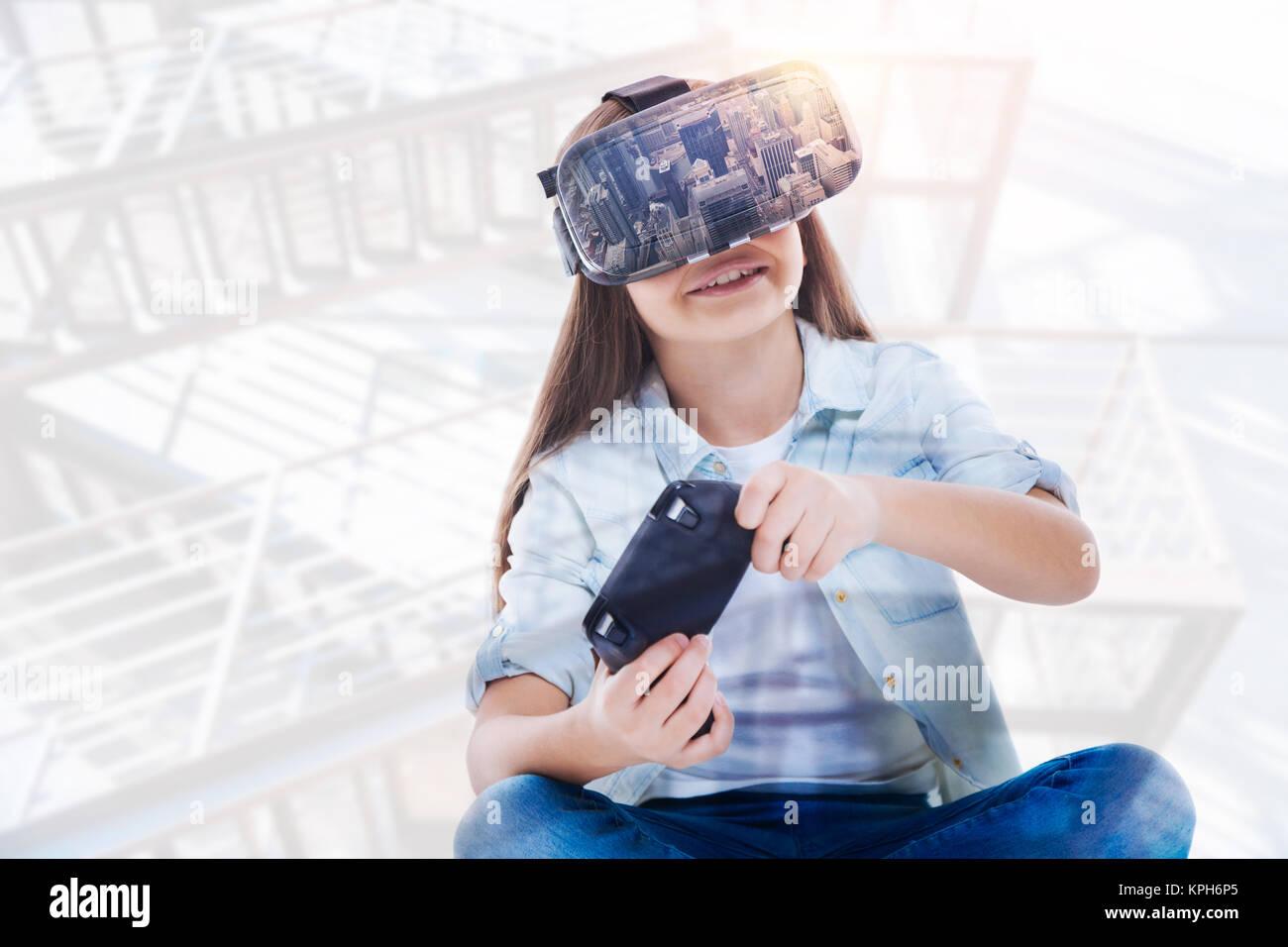 19d28e0e074 Vigorous optimistic girl playing in VR game - Stock Image
