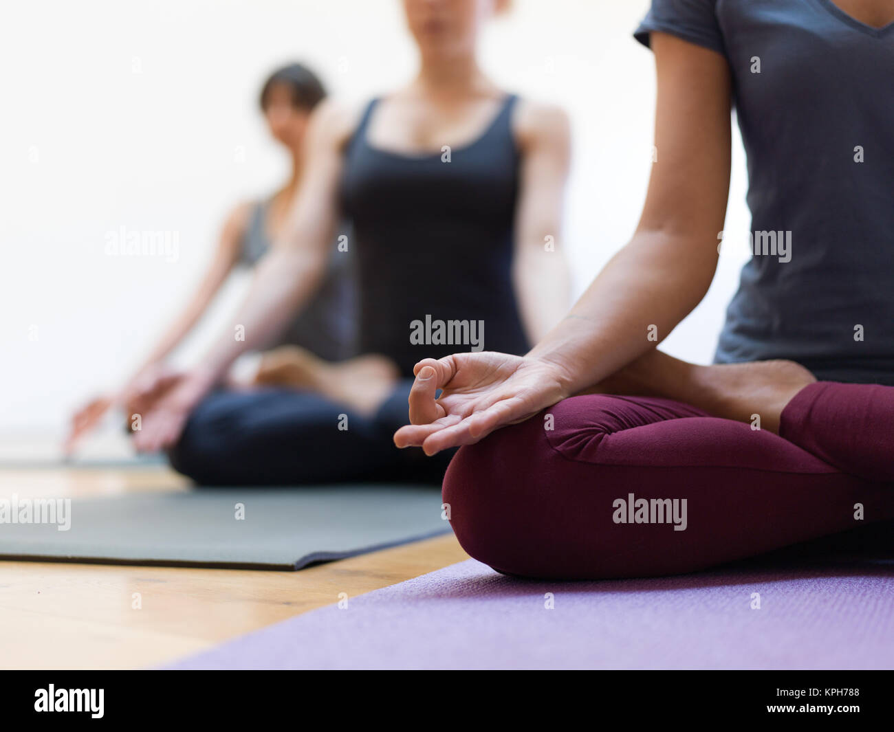 Women practicing yoga together and sitting in the lotus pose: mindfulness meditation, spirituality and healthy lifestyle - Stock Image