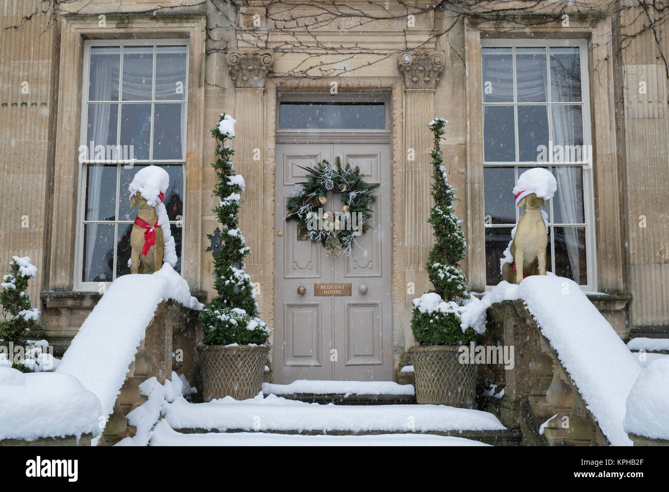 christmas dog statues and door wreath decoration in the snow outside
