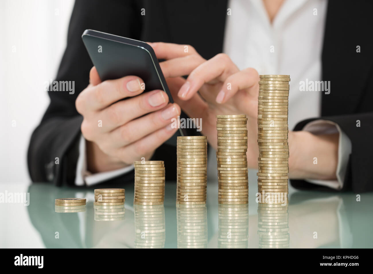 Businesswoman Using Smartphone With Stacked Coins On Desk - Stock Image