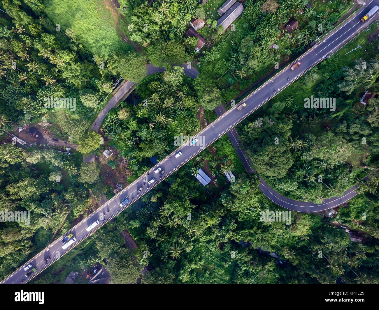 New highway (above) replace the old curvy road (bellow) in Tabanan Bali. This road is part of Indonesia's transformation - Stock Image