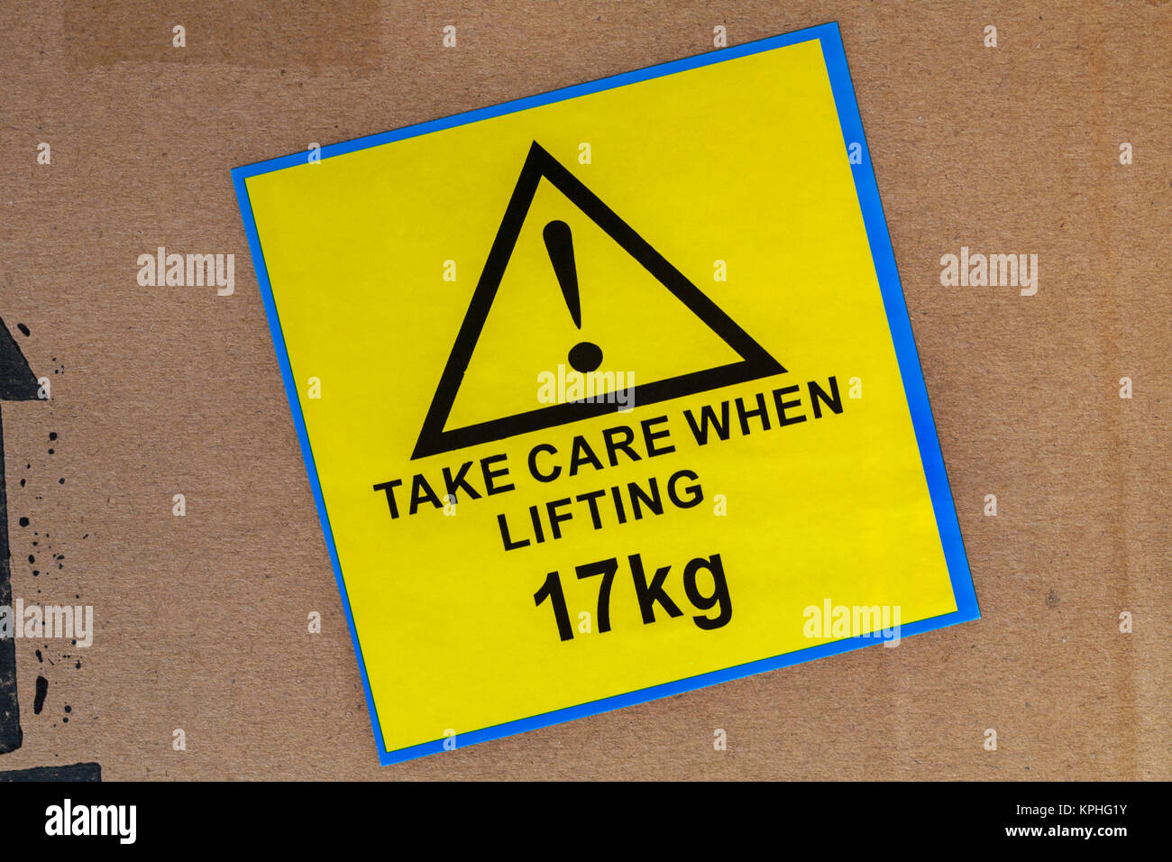 Take care when lifting 17kg yellow sticker label stuck on cardboard box - Stock Image