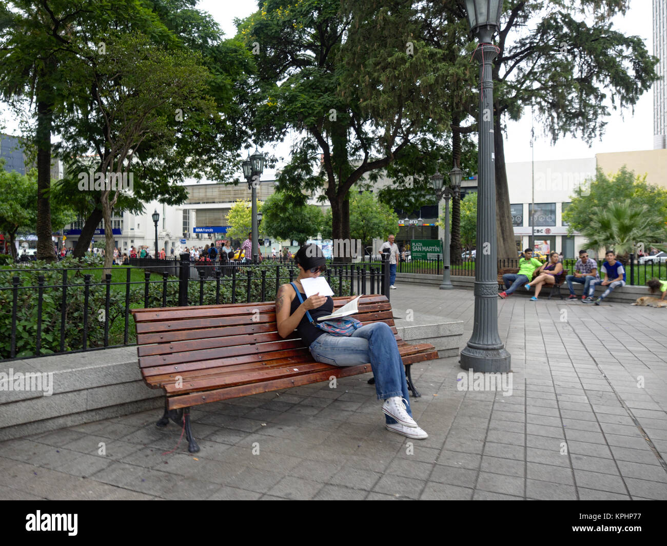 Cordoba, Argentina - 2017: A young woman reads a book on a bench at San Martin square, one of the main city landmarks. Stock Photo