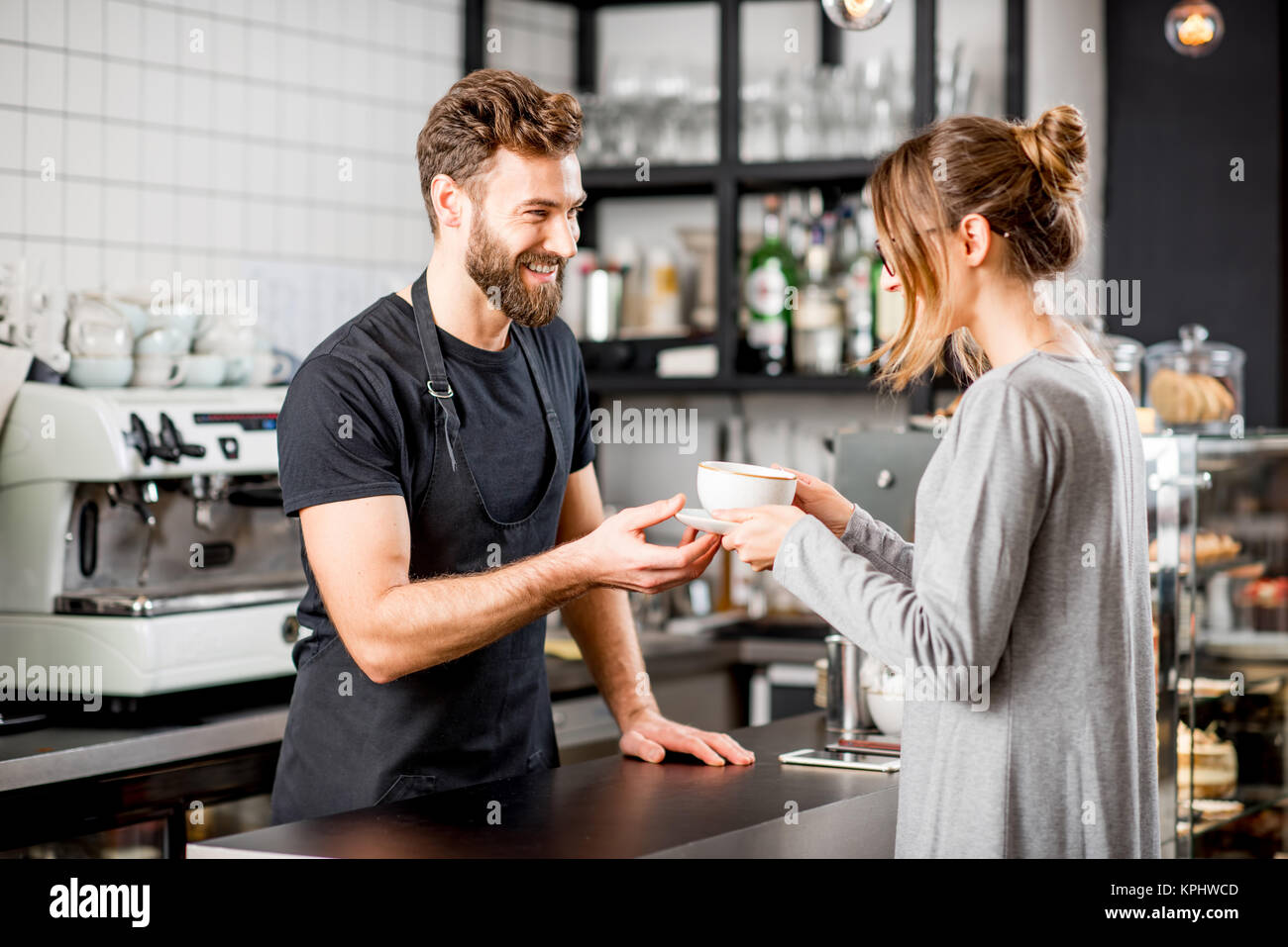 Barista with client at the cafe - Stock Image