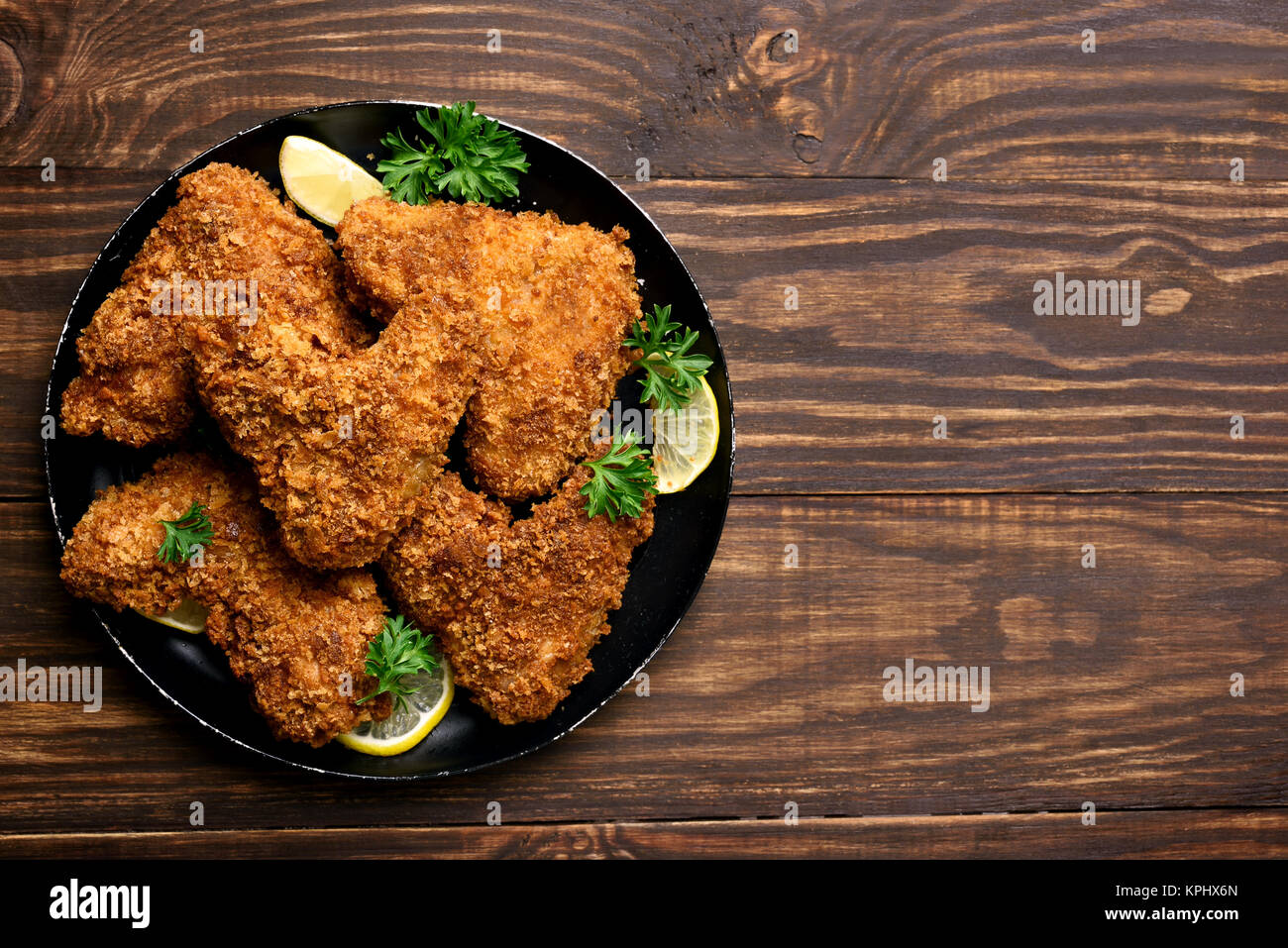 Fried breaded chicken wings on plate over wooden background with copy space. Top view, flat lay food - Stock Image