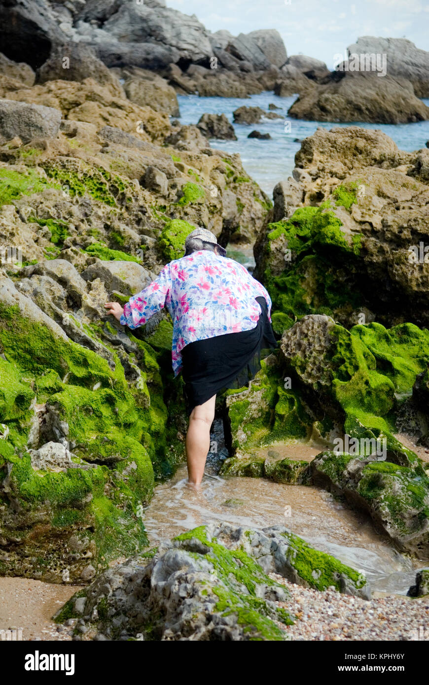 photo of my mother clambering over weed covered rocks near Sesimbra, Portugal - Stock Image