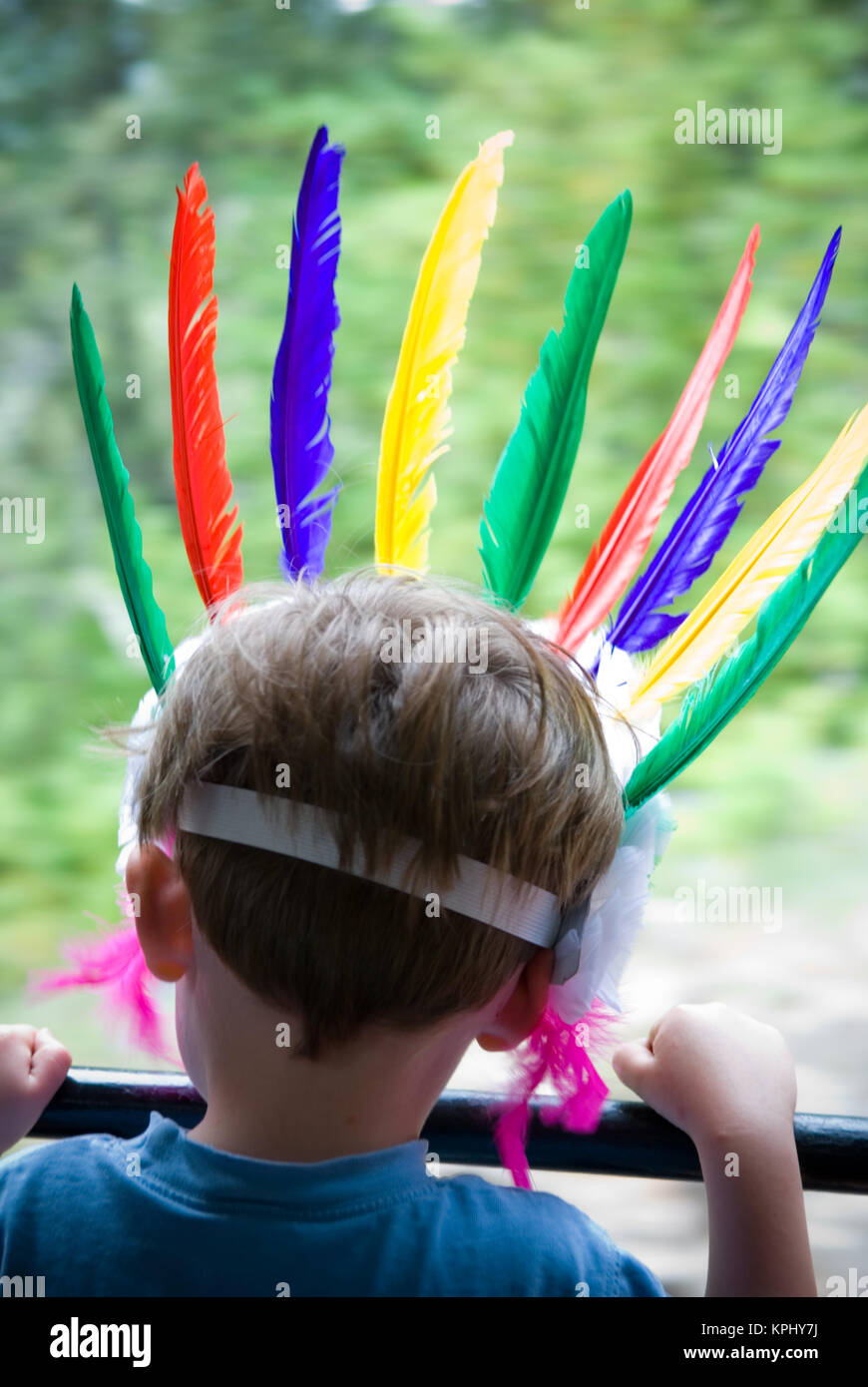 rear shot of young boy looking out of moving train's window with his head adorned with colourful feather headress - Stock Image