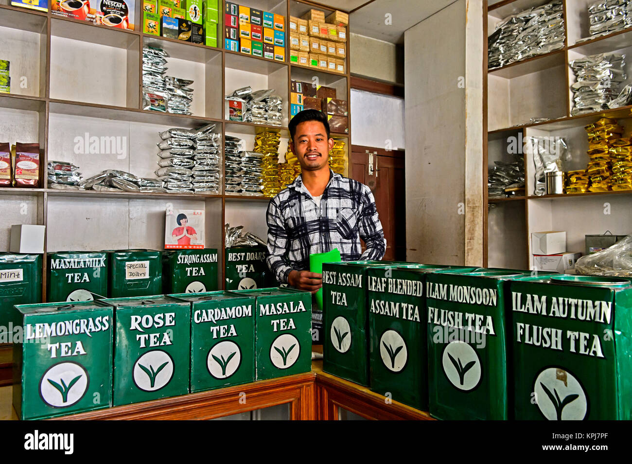 Tea merchant behind large tins with tea in his shop, Kathmandu, Nepal - Stock Image