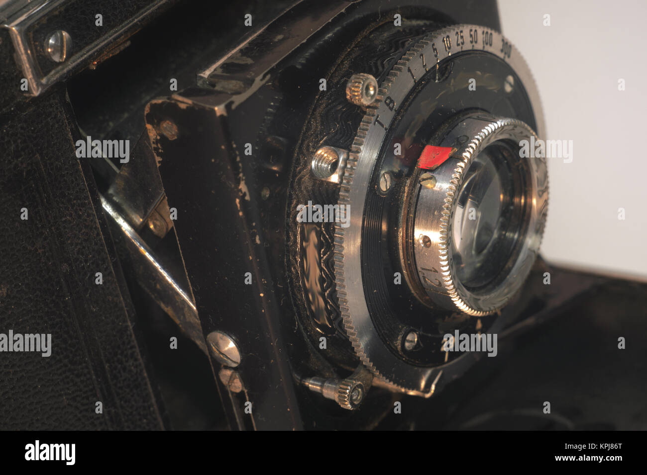fixed lens of vintage folding camera with bellows, front view - Stock Image