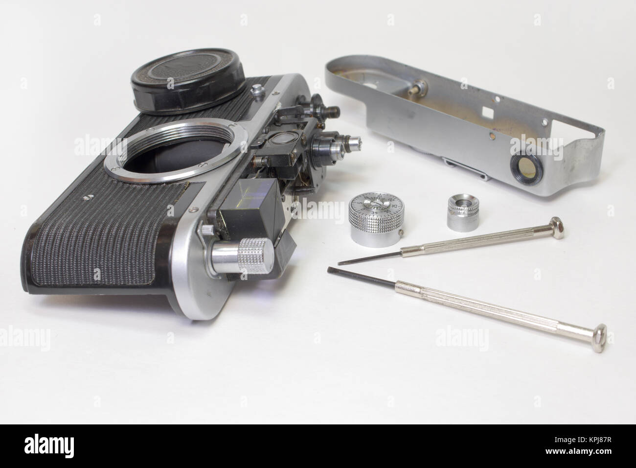vintage film camera, disassembled for inspection of rangefinder mechanism. Lens cover on a body Stock Photo