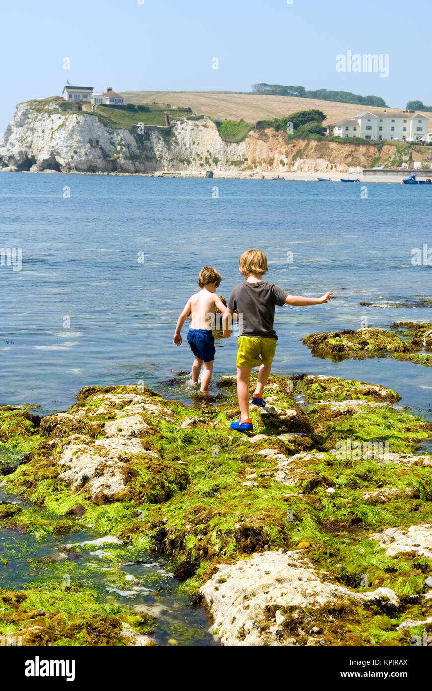 two young boys scramble over the rocks by the sea at low tide, Freshwater Bay, Isle of Wight, UK - Stock Image