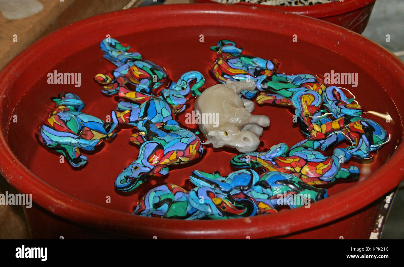 Colourful elephant shaped candles cooling in bucket of water, Kingdom of Swaziland. Stock Photo