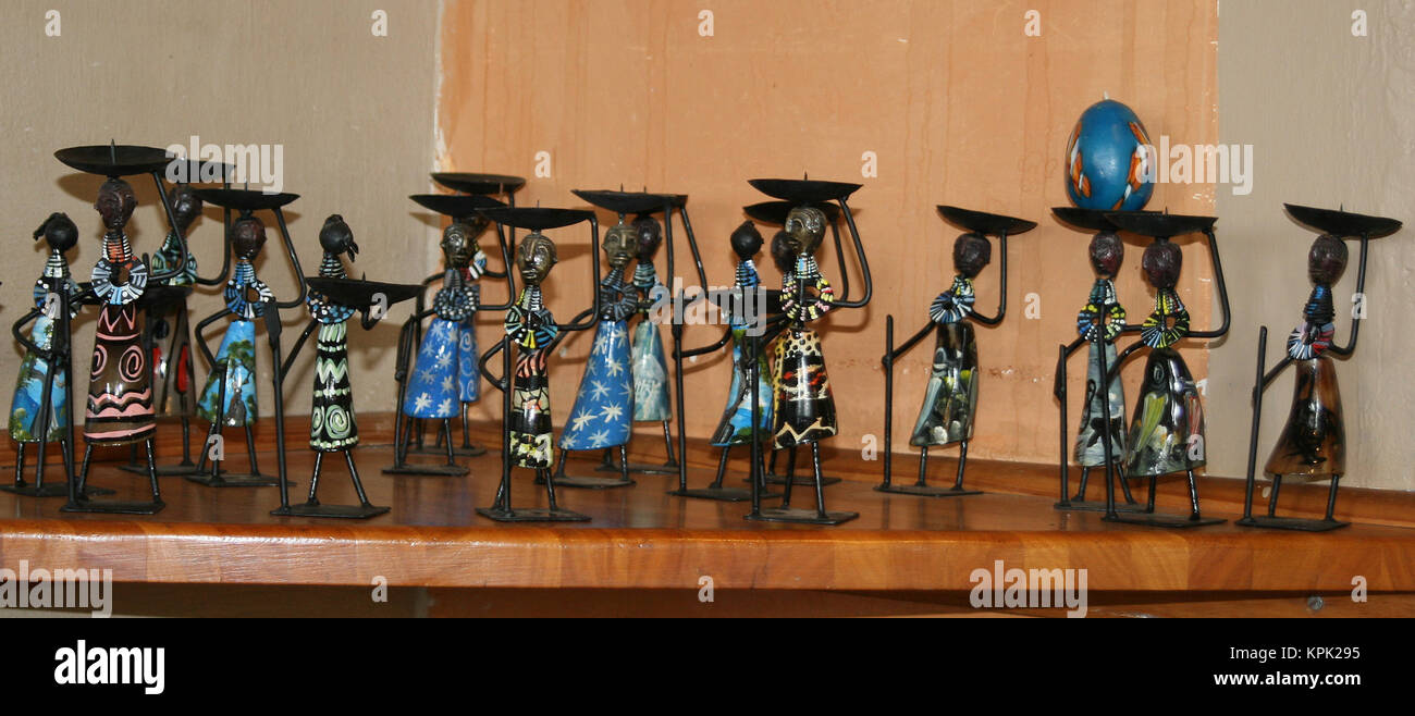 Traditional Swazi women candle holders on shelf against decorated wall, Kingdom of Swaziland. - Stock Image