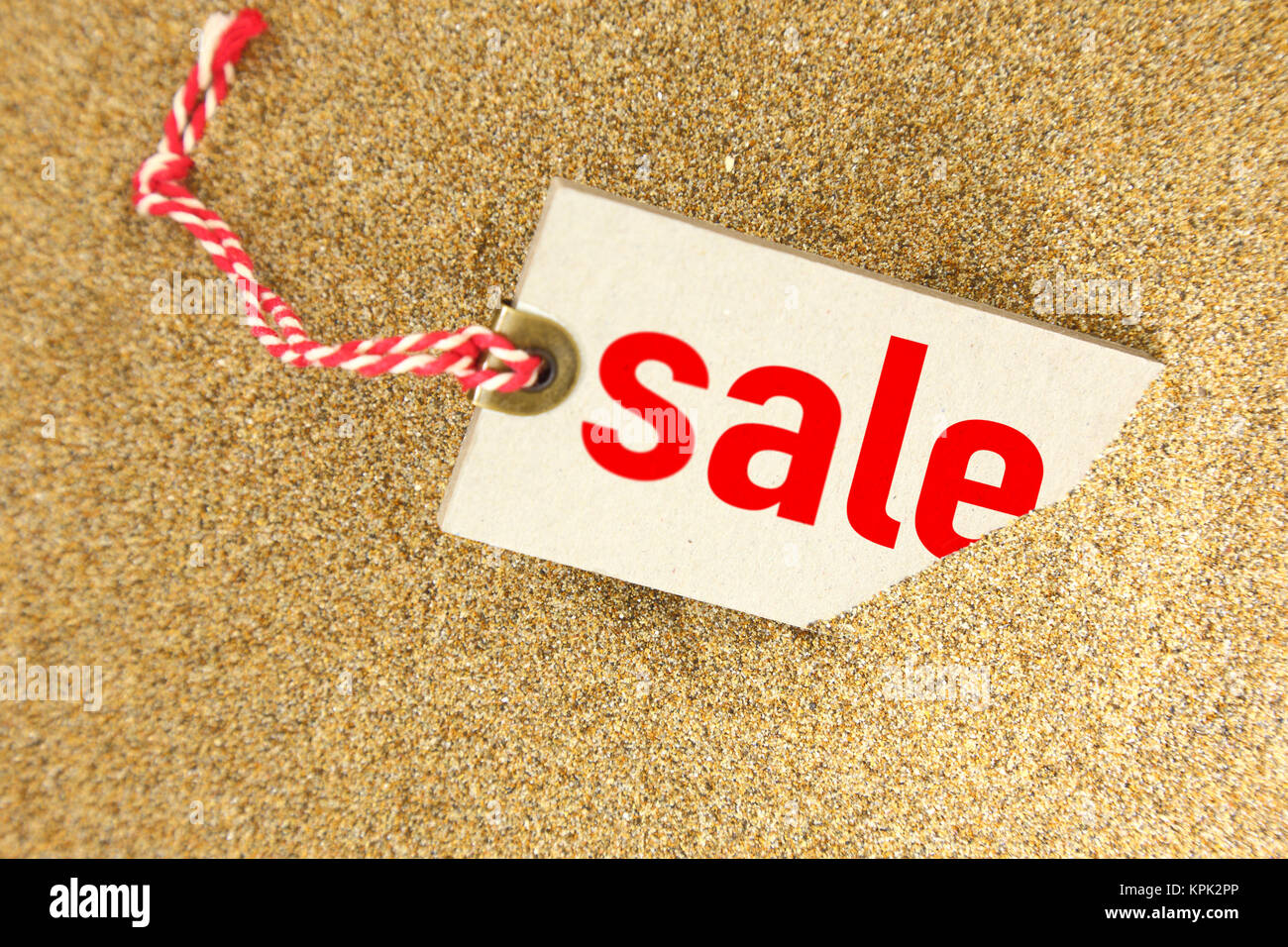 Big sale tag on sand closeup - Stock Image