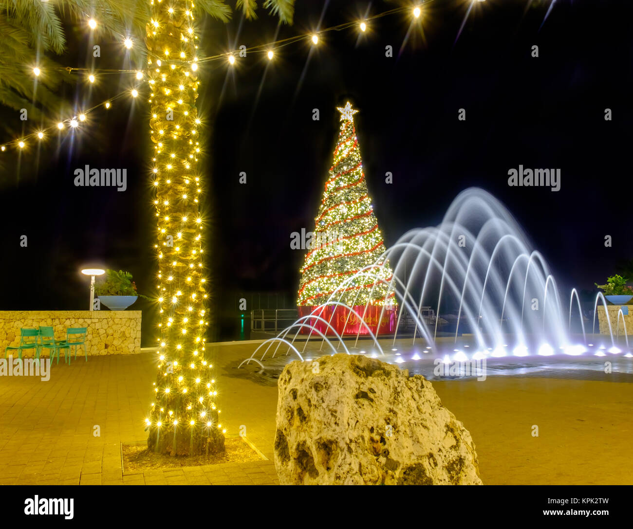 A Christmas tree, a water fountain and a illuminated palm tree with strip lights on a pedestrian street of Camana - Stock Image