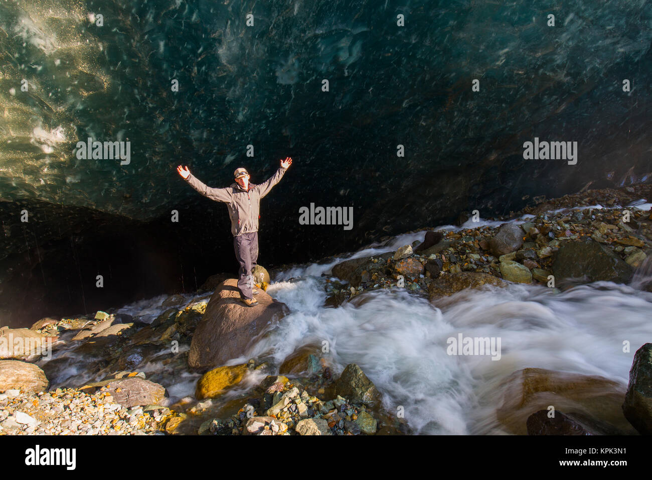 A man poses on a boulder with arms outstretched in front of a cave beneath the ice of Root Glacier in Wrangell-St. - Stock Image