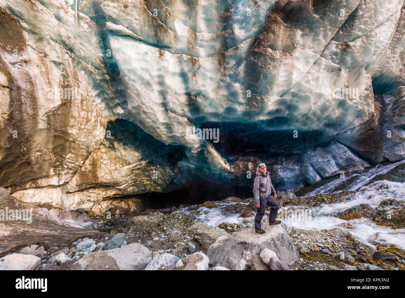 A man surrounded by rushing water poses in front of a cave beneath the ice of Root Glacier in Wrangell-St. Elias - Stock Image