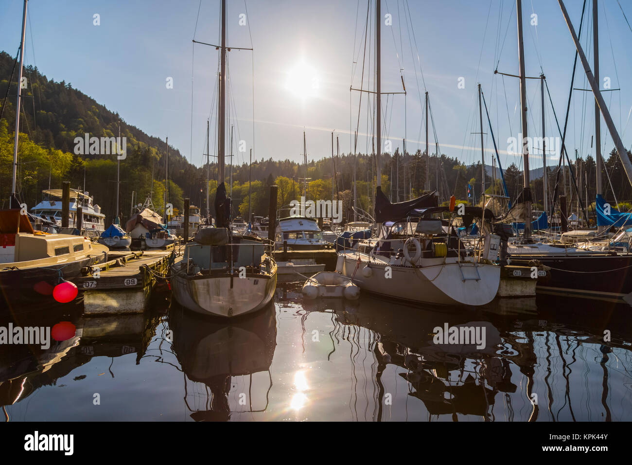 A tranquil sunny afternoon  as the sun sets behind the marina at Snug Cove, Bowen Island on the West Coast near - Stock Image