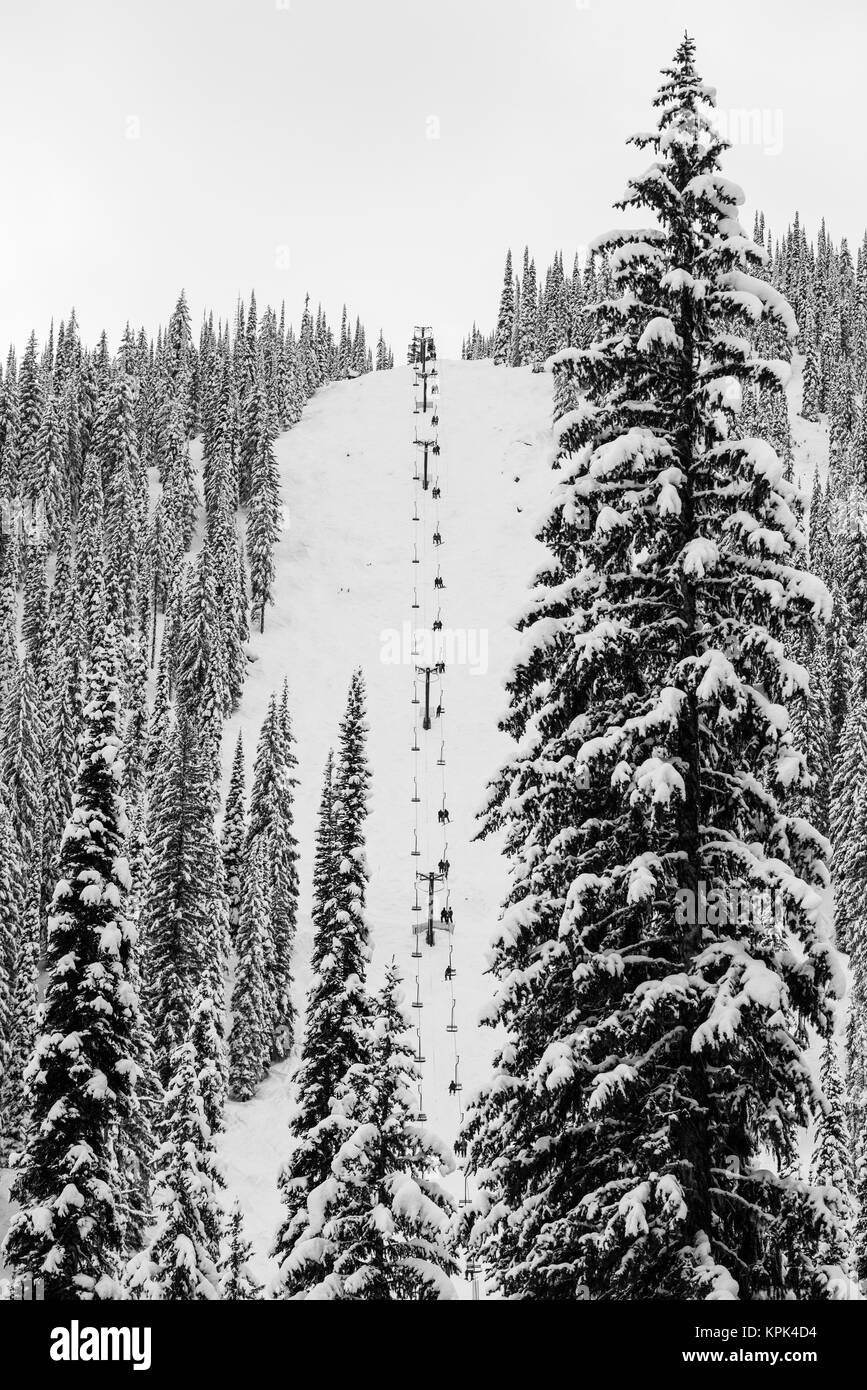A chair lift going up a steep slope on a snow covered ski hill at Whitewater Resort; Nelson, British Columbia, Canada - Stock Image