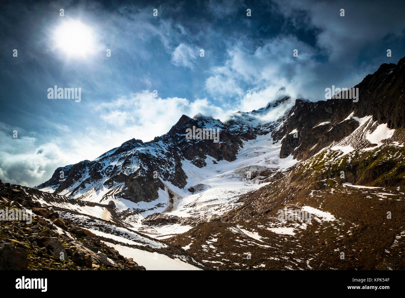 Storm clouds over Aiguille des Glaciers (mountain) and Estellette Glacier and moraine, Alps; Aosta Valley, Italy Stock Photo