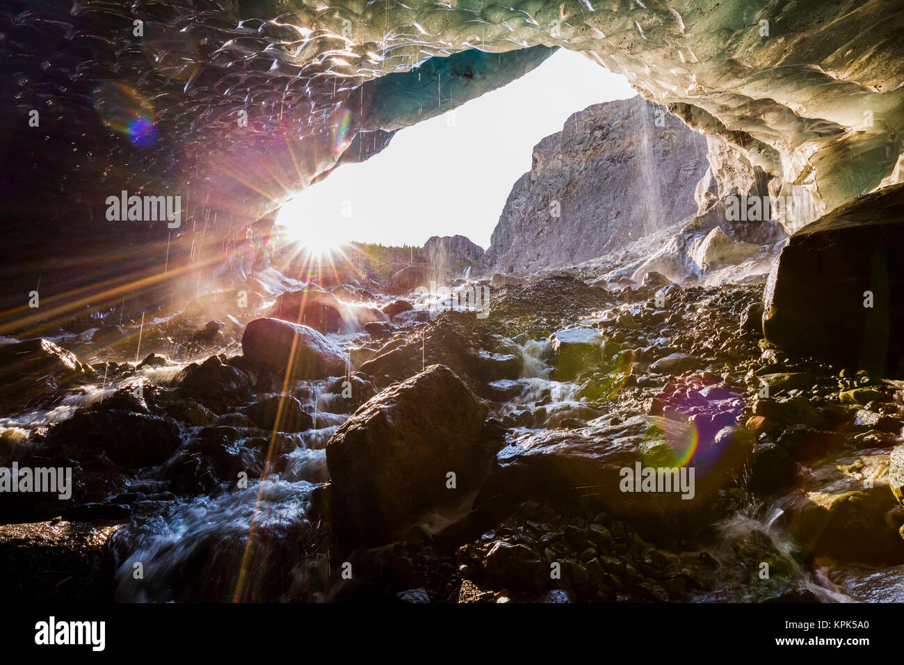 The sun shines into a cave beneath the ice of Root Glacier in Wrangell-St. Elias National Park; Alaska, United States Stock Photo