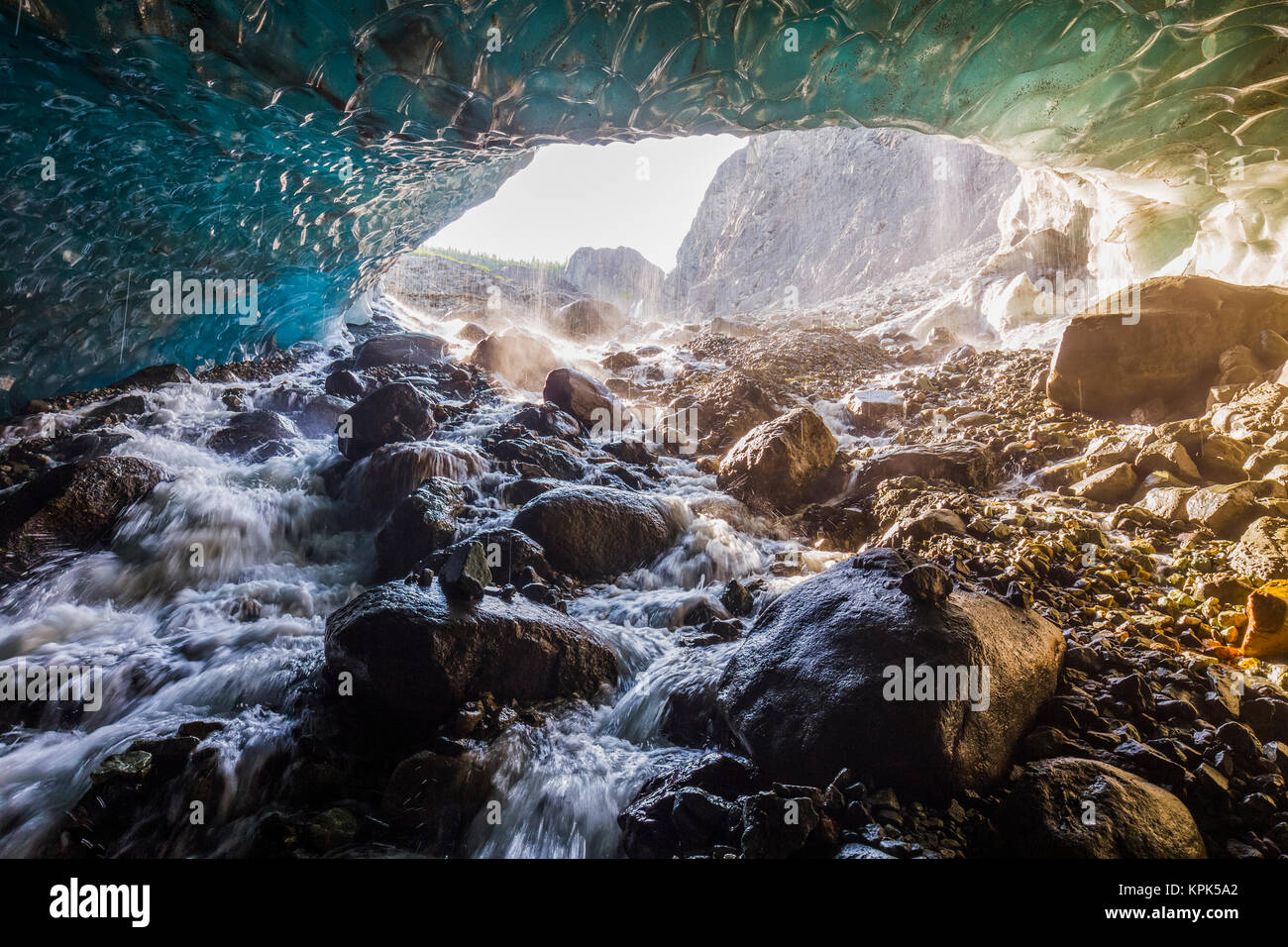 Water cascades over rocks inside a cave beneath the ice of Root Glacier in Wrangell-St. Elias National Park; Alaska, - Stock Image