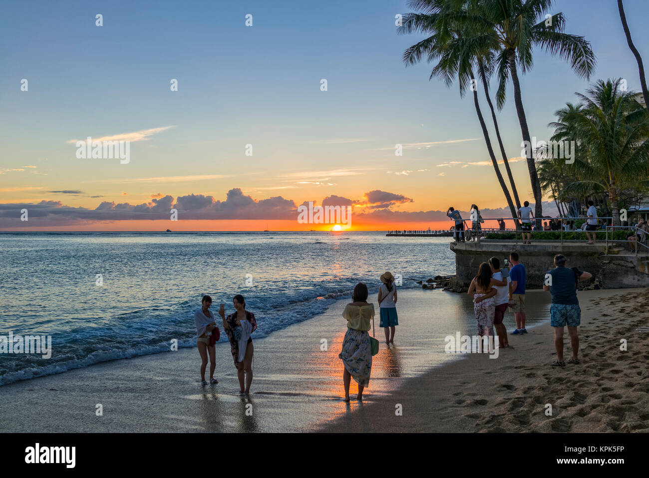 Tourists Watch And Photograph Sunset On Waikiki Beach