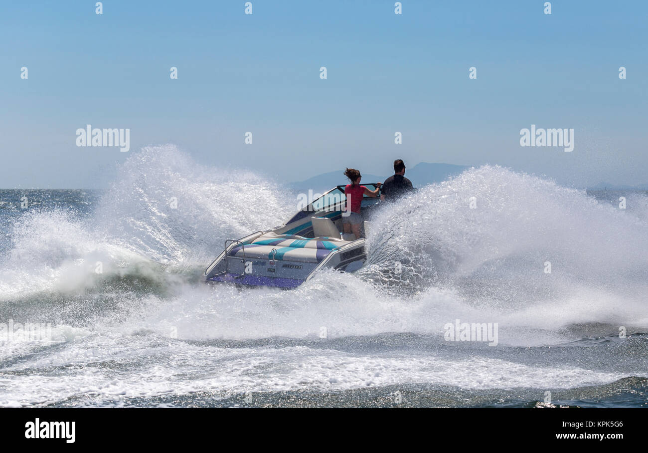 A speedboat hits a large ocean wave sending out a huge splash as the driver and passenger stand at the bow looking - Stock Image