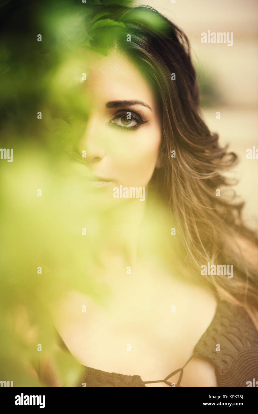 Beautiful young woman hiding in the bushes - Stock Image