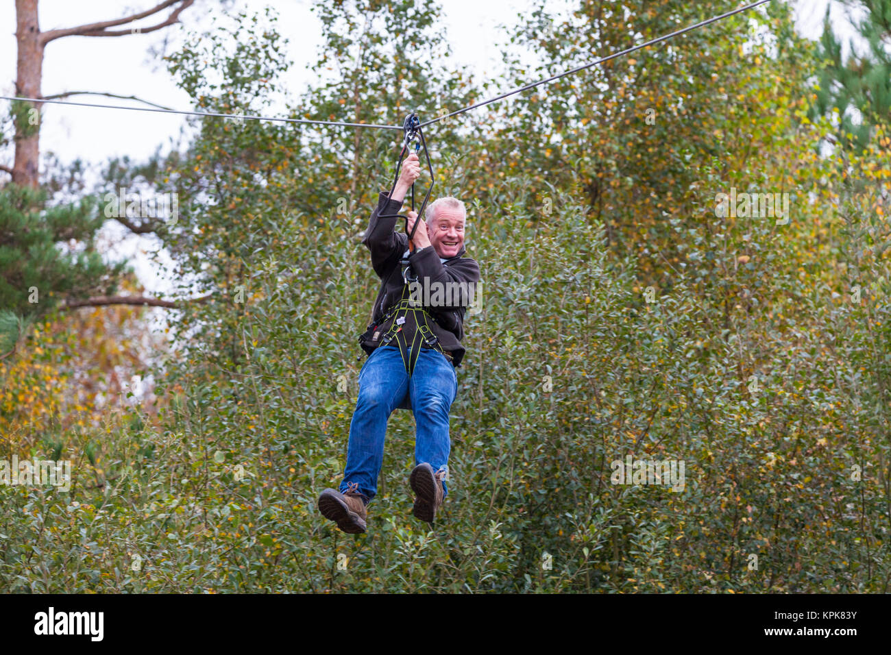 A man on a zipwire with a big grin on his face, Bedgebury National Pinetum at Bedgebury, Kent - Stock Image