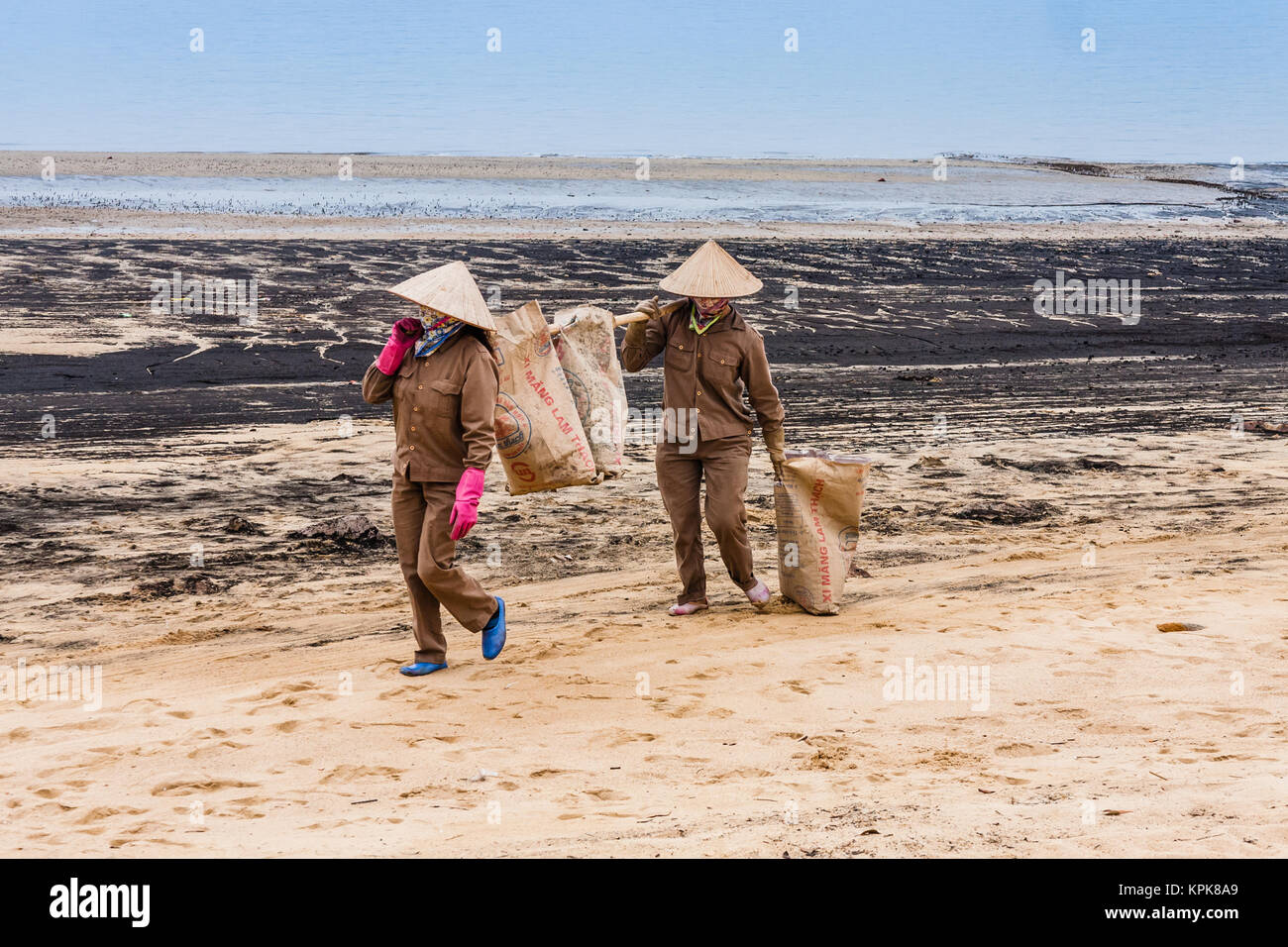 Vietnamese workers cleaning the beach on Ngọc Châu, Ha Long Bay - Stock Image