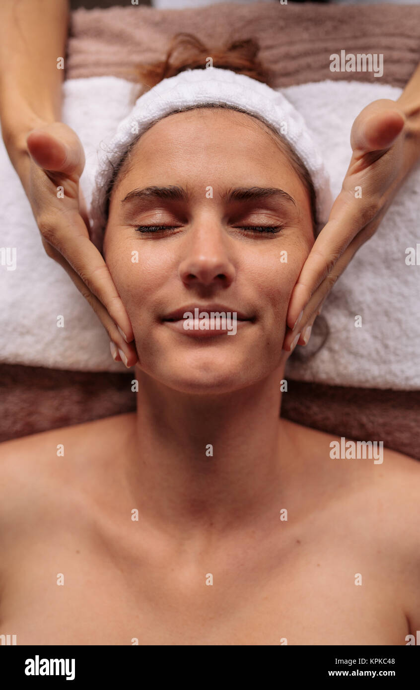 Close up of a woman getting facial beauty treatment in spa salon. Beautiful young woman getting a face massage. - Stock Image