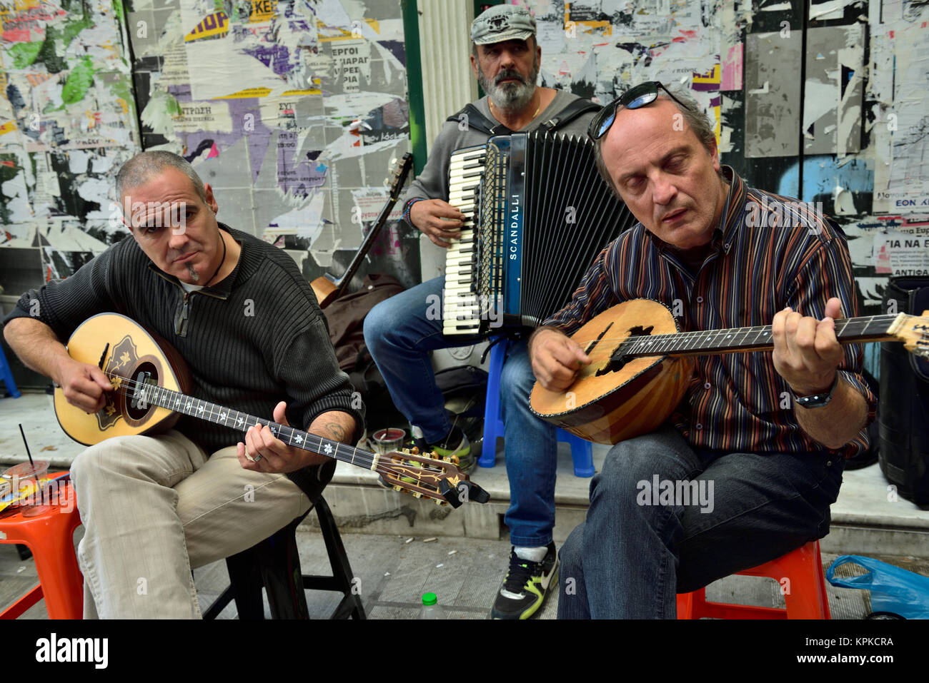 Group of three musician buskers playing traditional instruments along pavement in central Athens, Greece - Stock Image