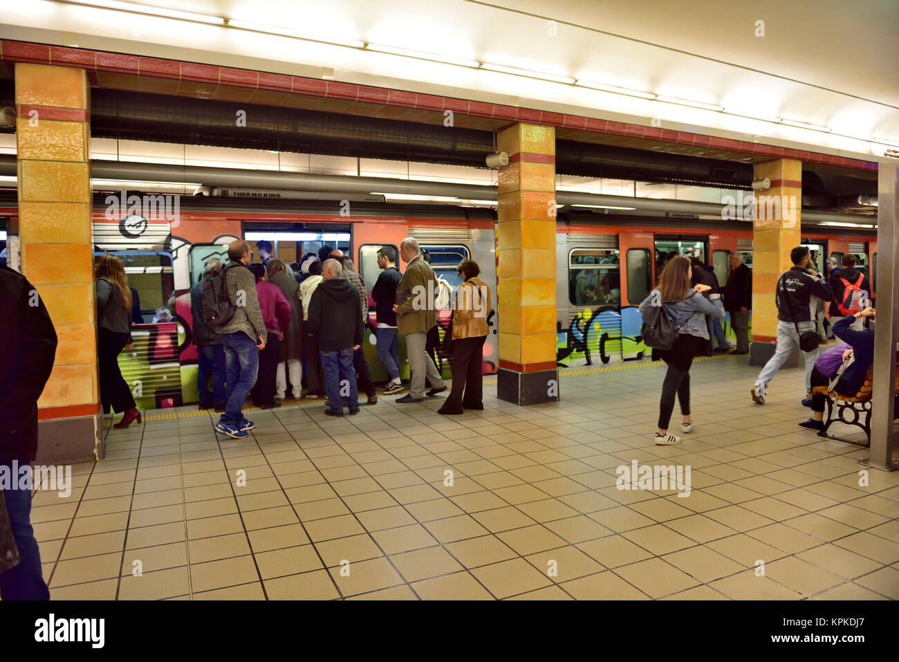 Passengers on platform waiting for and boarding train at Omonia metro station, Athens, Greece - Stock Image