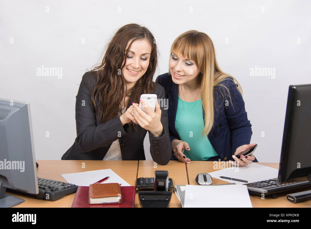 Two branchless workers enthusiastically looking at cell phone at his desk - Stock Image