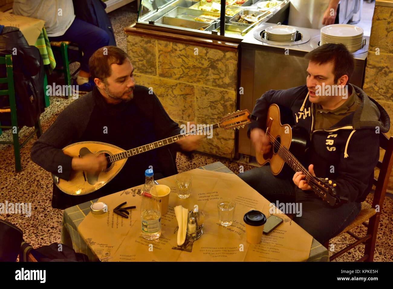Two musicians busking inside restaurant one with traditional Greek bouzouki the other with guitar - Stock Image