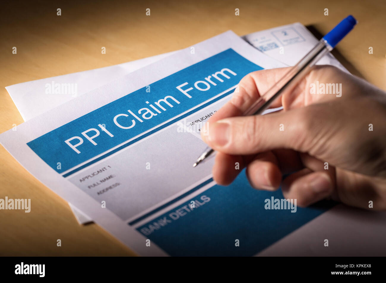 A man filling in a PPI (payment protection insurance) claim form - Stock Image