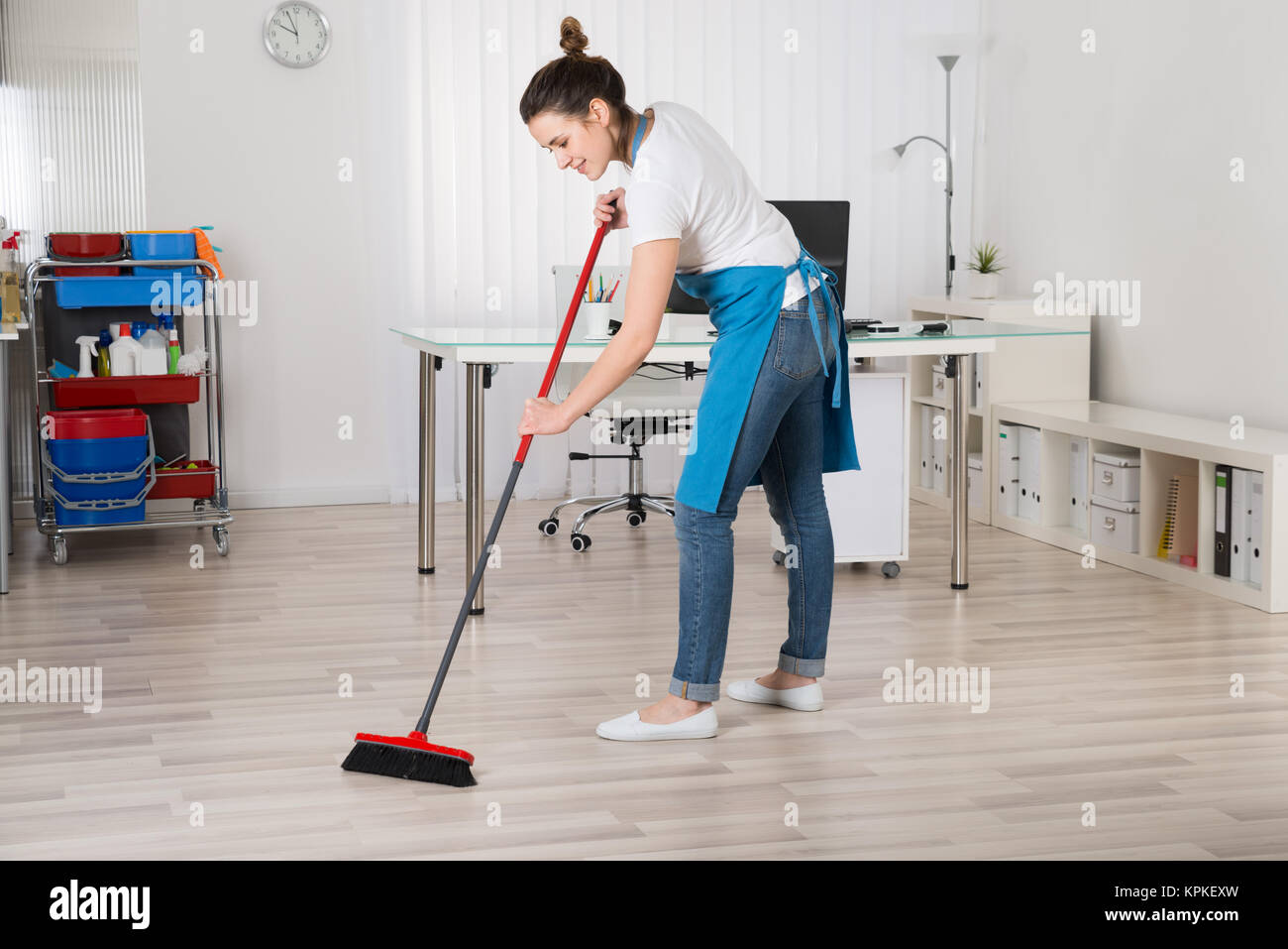 Female Janitor Sweeping Floor With Broom - Stock Image