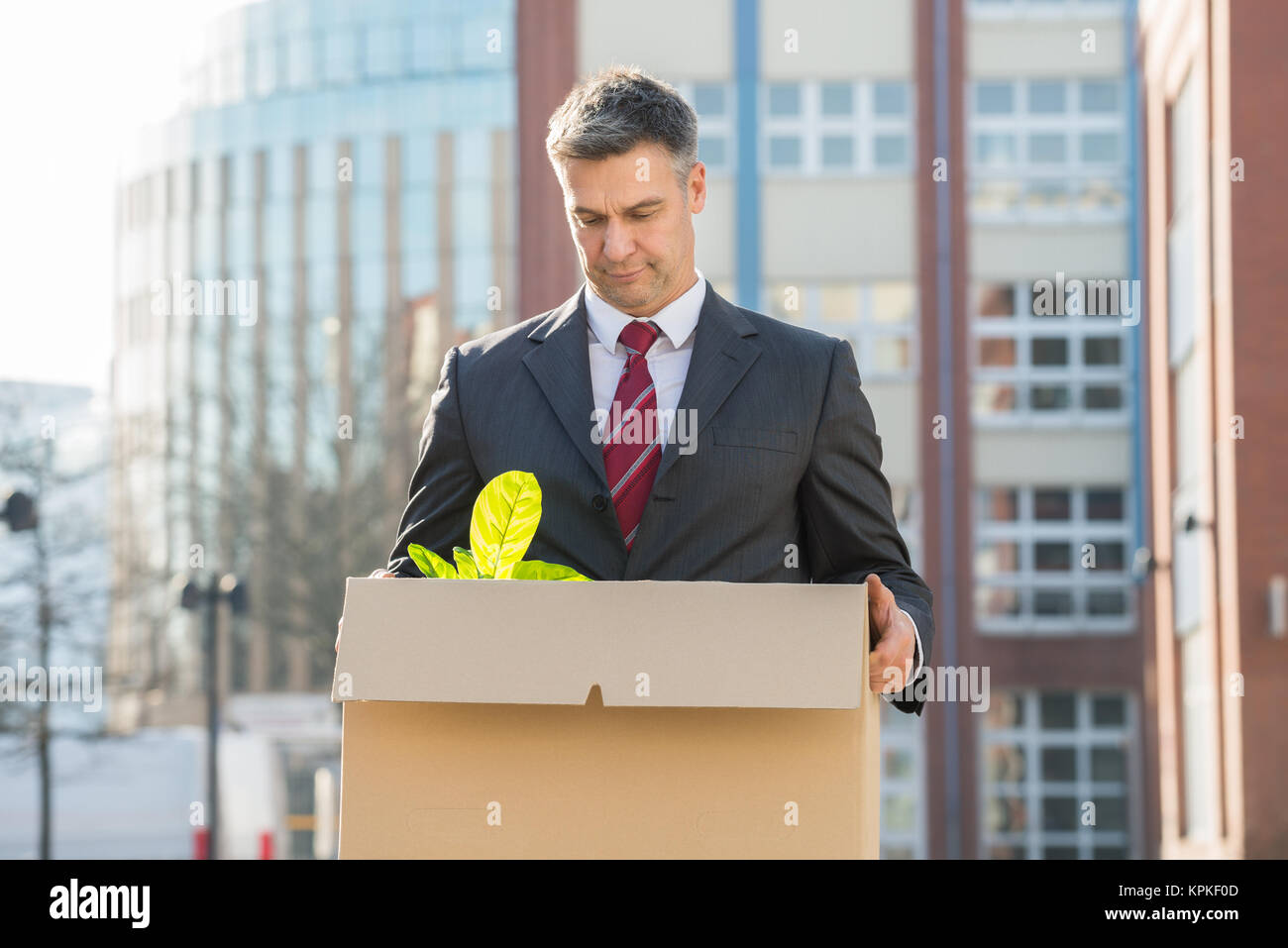 Businessman Standing With Cardboard Box Outside Office - Stock Image
