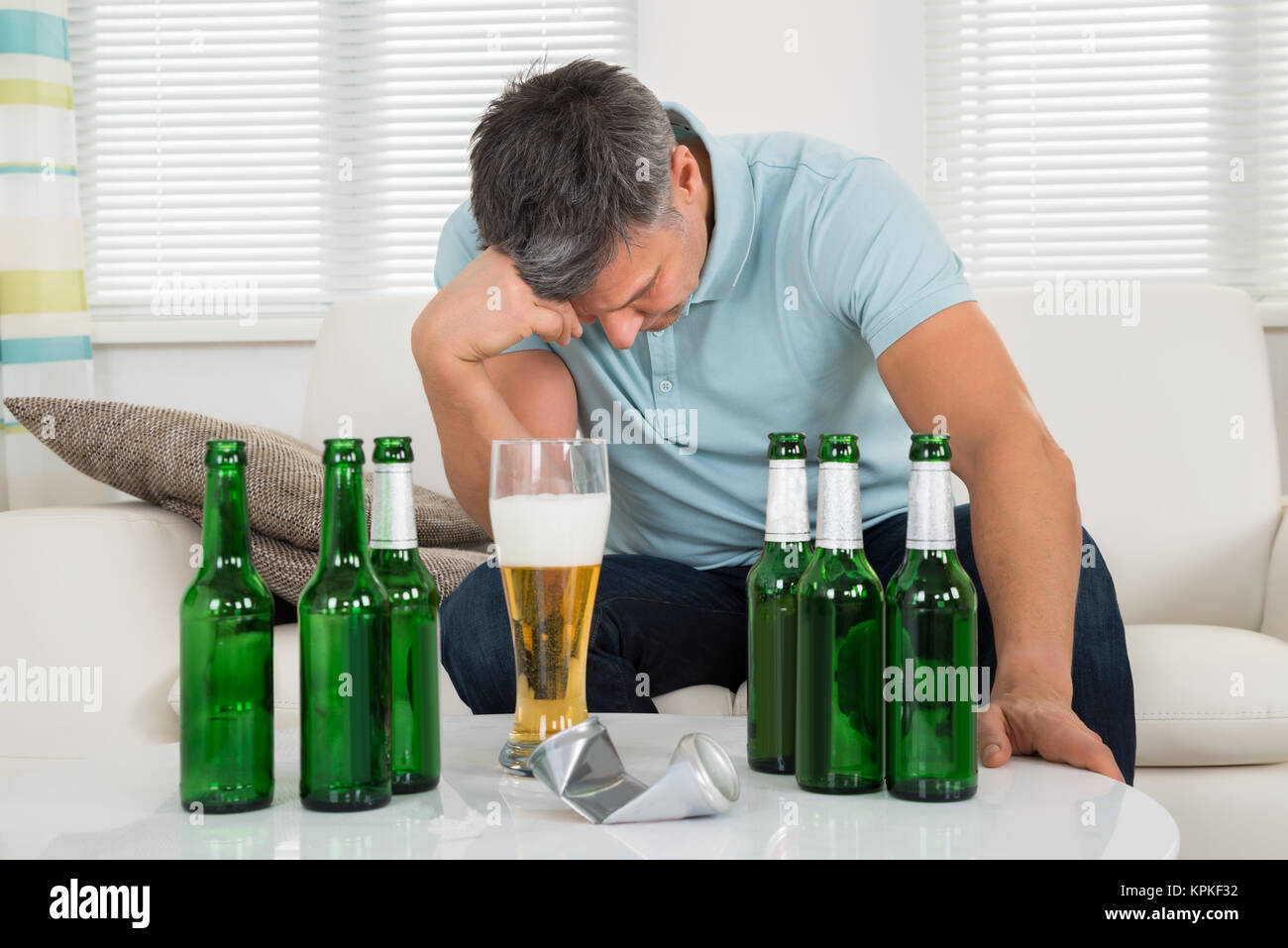 Man Sitting On Sofa In Front Of Beer Stock Photo