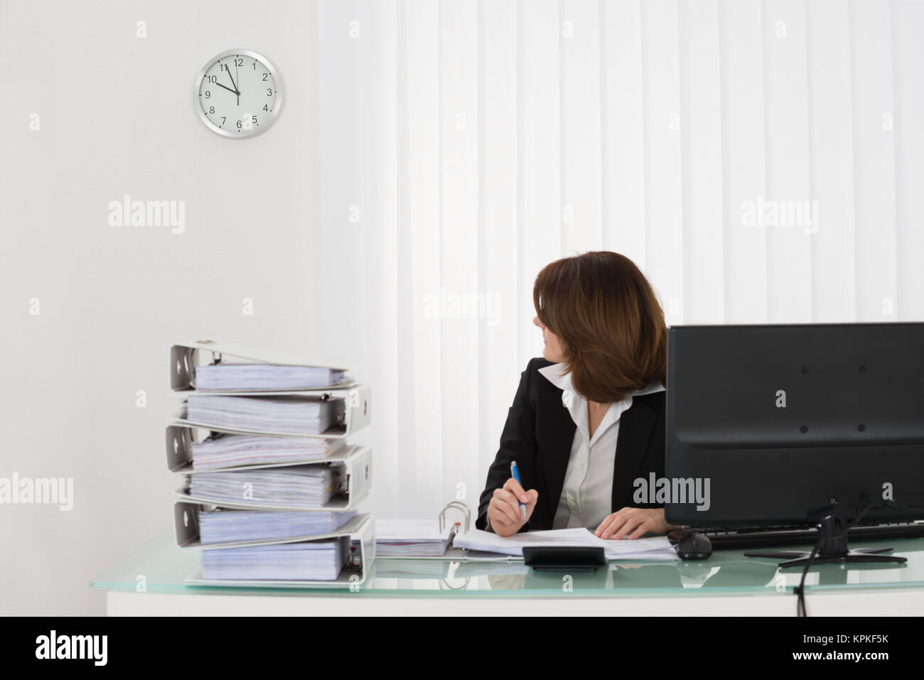 Businesswoman Looking At Clock - Stock Image