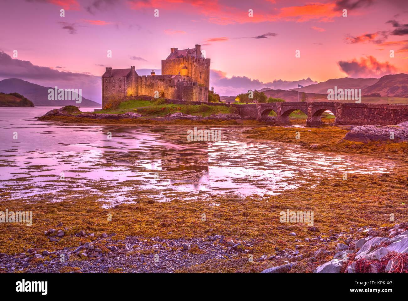 Magenta sunset at Eilean Donan Castle, Dornie, Kyle of Lochalsh in Scotland, United Kingdom. The most visited castle - Stock Image