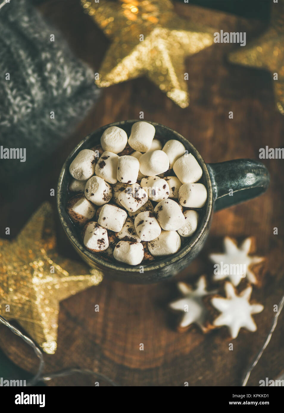 Christmas winter hot chocolate with marshmellows served with light garland - Stock Image