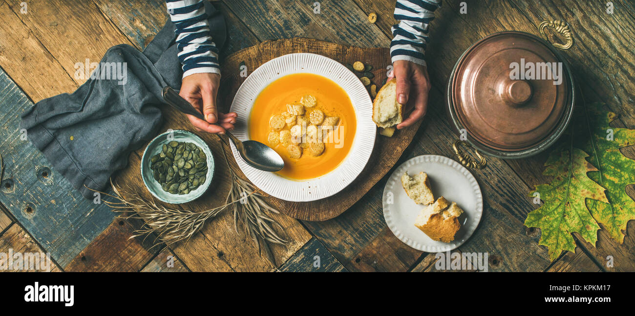 Fall warming pumpkin cream soup, top view, wide composition - Stock Image