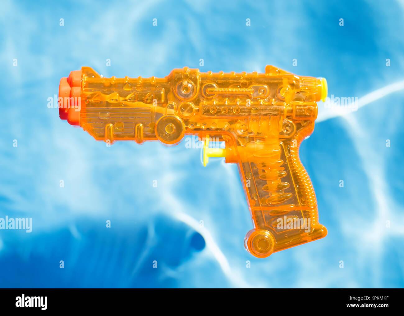 Orange squirt gun floating in water. - Stock Image
