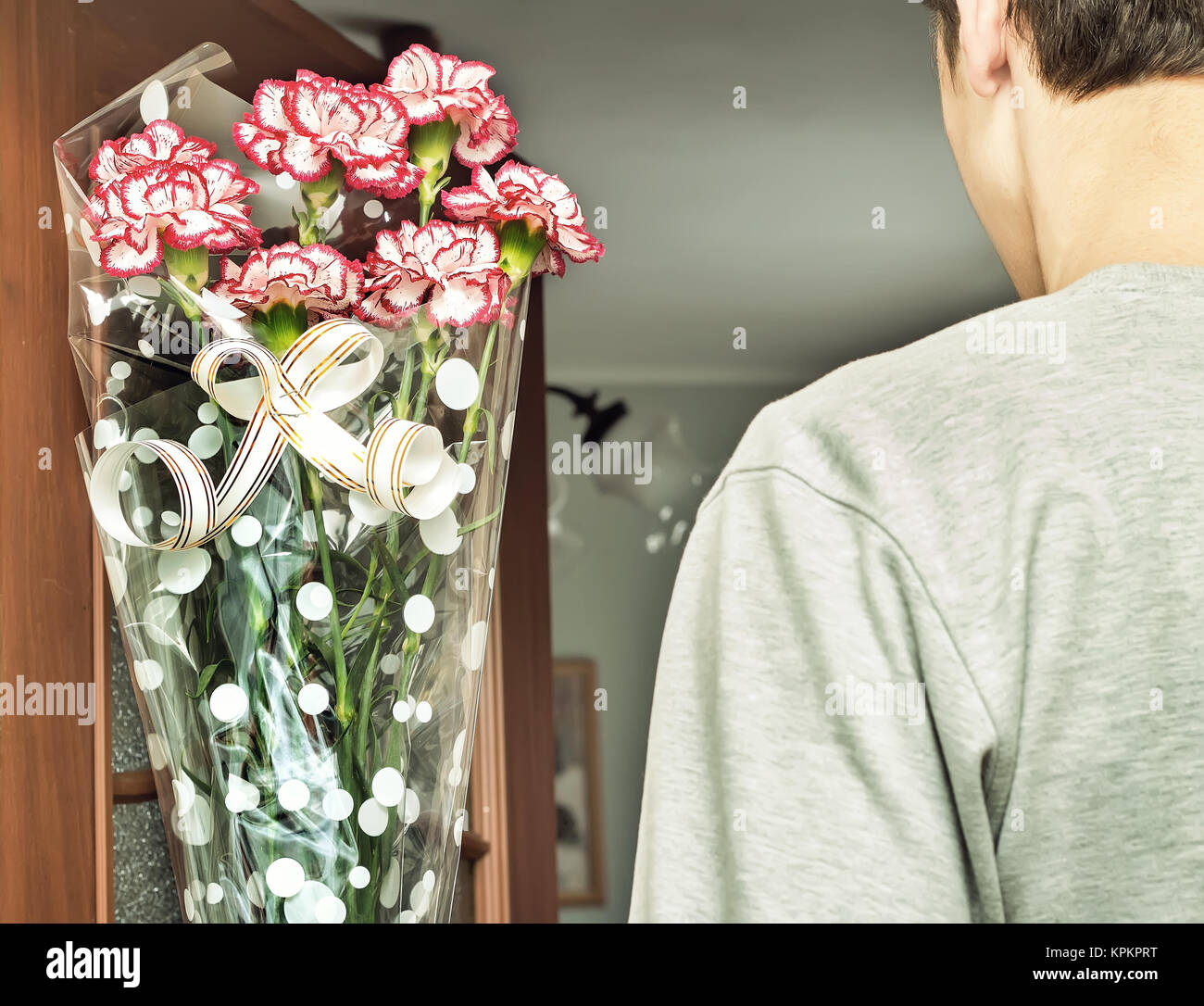 A young man with a bouquet of flowers in his hands. - Stock Image