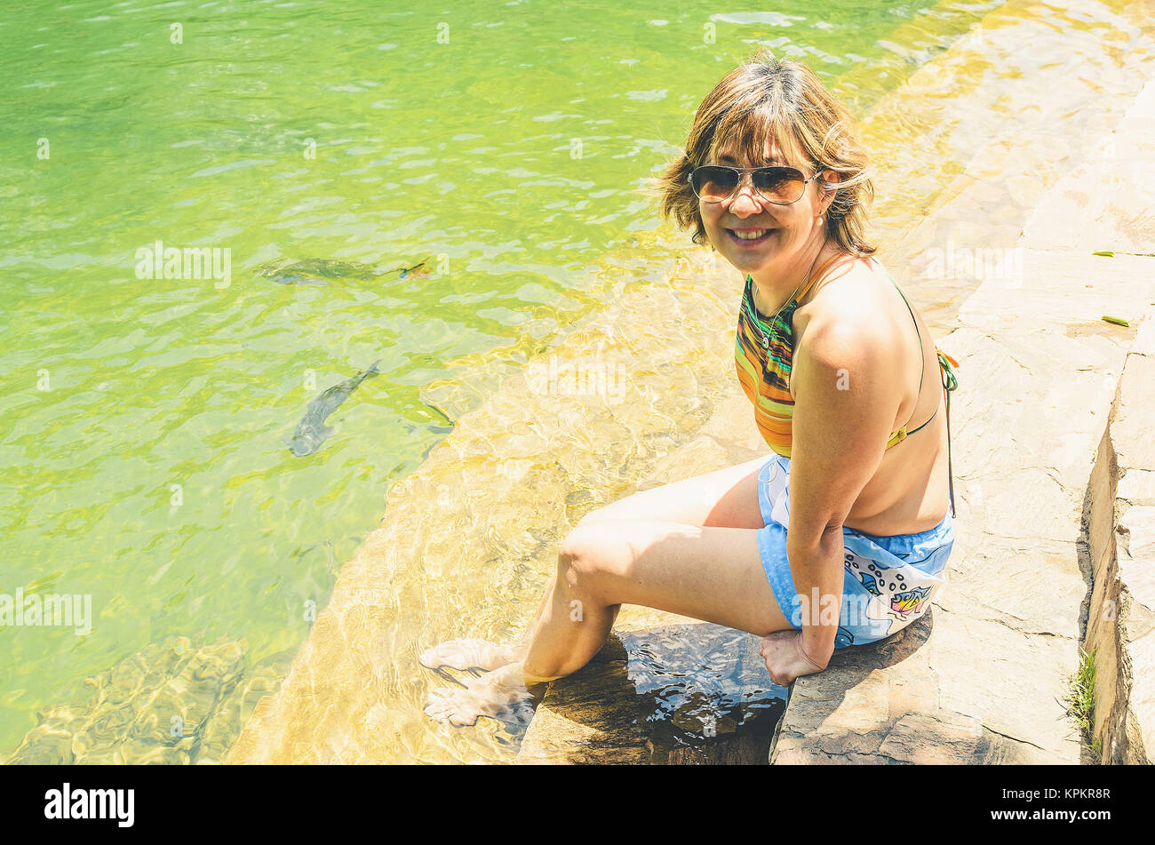 Woman tourist seated on the margin of the river Formoso with some piraputanga fishes swimming on the transparent - Stock Image