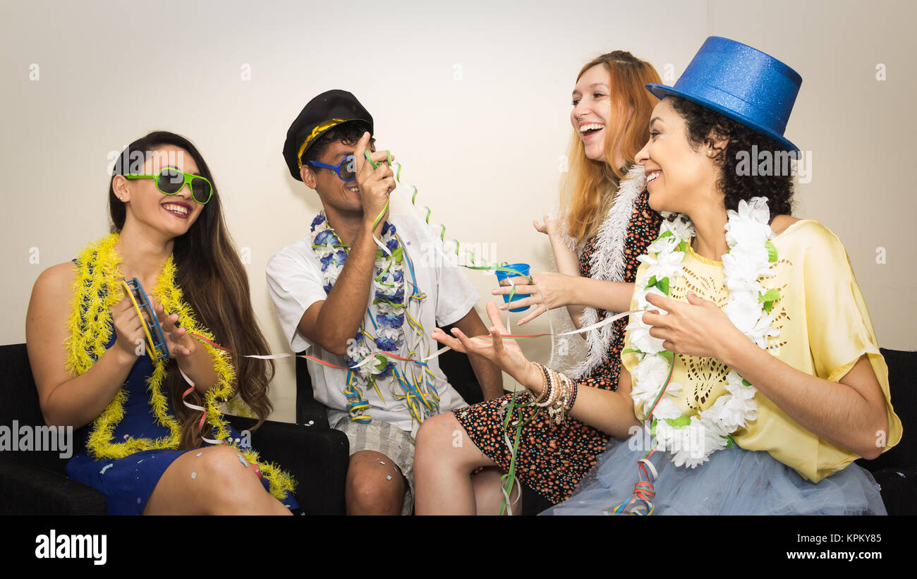 Multi ethnic group of friends are making Carnaval party. Euphoria in Brazil. They are wearing costumes, top hats, - Stock Image