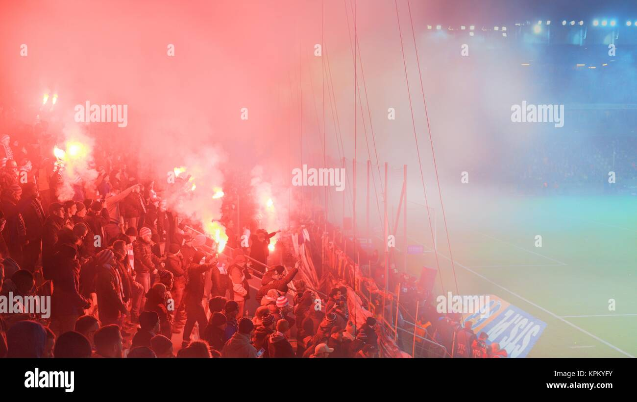 KRAKOW, POLAND-DECEMBER 13, 2017: Polish soccer fans lighting smoke flares at Cracovia Stadium, during the Polish - Stock Image