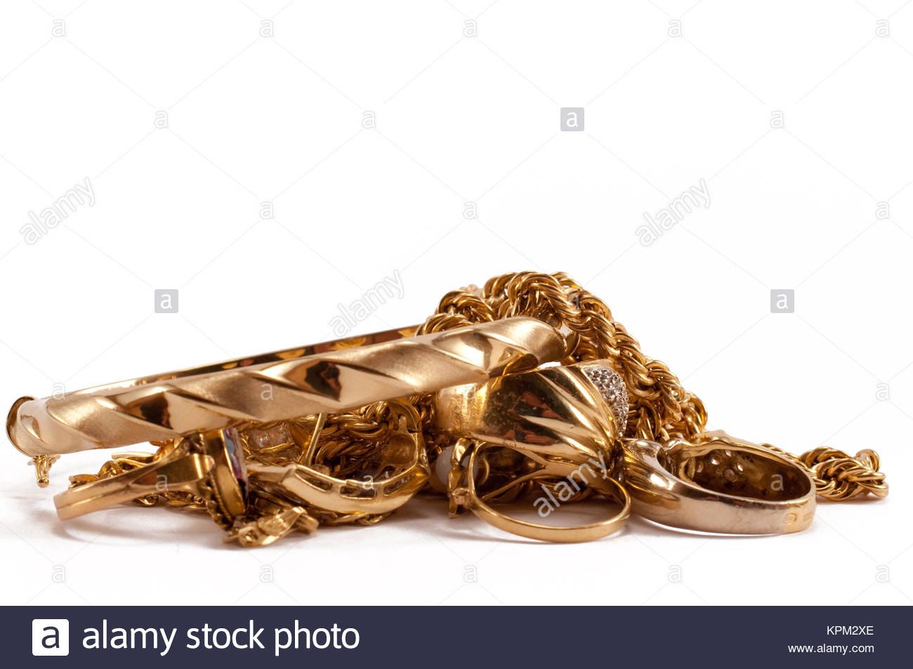scrap gold jewellery including chains, bracelets and rings on a white background - Stock Image
